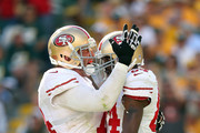 Joe Staley #74 and Randy Moss #84 of the San Francisco 49ers celebrate after Moss caught a touchdown pass during the NFL season opener against the Green Bay Packers at Lambeau Field on September 9, 2012 in Green Bay, Wisconsin.