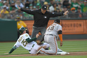 Third base umpire Pat Hoberg #31 gives the safe call for Stephen Piscotty #25 of the Oakland Athletics after Piscotty stole third base sliding past the tag of Pablo Sandoval #48 of the San Francisco Giants in the bottom of the second inning at Oakland Alameda Coliseum on July 21, 2018 in Oakland, California.