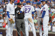 (L-R) Kris Bryant #17, Addison Russell #27, Javier Baez #9 and Anthony Rizzo #44 of the Chicago Cubs share a laugh with second base umpire Eric Cooper #56 during a pitching change against the San Francisco Giants at Wrigley Field on May 25, 2018 in Chicago, Illinois. The Cubs defeated the Giants 6-2.