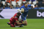 Alex Goode of Saracens tackled by Jamie Roberts and Demetri Catrakilis of Harlequins during the Aviva Premiership match between Saracens and Harlequins at London Stadium on March 24, 2018 in London, England.