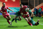 Kristian Phillips of Scarlets crashes through the tackles of Ben Youngs and Owen Williams of Leicester Tigers during the  European Rugby Champions Cup match between Scarlets and Leicester Tigers at Parc y Scarlets on October 25, 2014 in Llanelli, Wales.