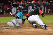 Jean Segura #2 of the Seattle Mariners slides safely into home on a sacrifice fly by Kyle Seager #15 as Alex Avila #5 of the Arizona Diamondbacks attempts a swipe tag during the third inning at Chase Field on August 24, 2018 in Phoenix, Arizona. The players are wearing special jerseys as part of MLB Players Weekend.