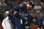 Nelson Cruz #23 gets a hug from Kyle Seager #15 of the Seattle Mariners after hitting a three run home run in the fourth inning of the game against the Los Angeles Angels of Anaheim at Angel Stadium on September 13, 2018 in Anaheim, California.