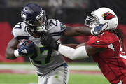 Running back Mike Davis #27 of the Seattle Seahawks stiff arms linebacker Gerald Hodges #51 of the Arizona Cardinals during the second quarter at State Farm Stadium on September 30, 2018 in Glendale, Arizona.