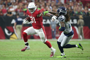 Running back David Johnson #31 of the Arizona Cardinals slips by cornerback Shaquill Griffin #26 of the Seattle Seahawks during the second quarter at State Farm Stadium on September 30, 2018 in Glendale, Arizona.