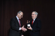 U.S. Senate Democratic Leader Chuck Schumer  (left) (D-NY), presents U.S. Senate Majority Leader Mitch McConnell (right) (R-KY) with a bottle of bourbon at the University of Louisville's McConnell Center where Schumer was scheduled to speak February 12, 2018 in Louisville, Kentucky. Sen. Schumer spoke at the event as part of the Center's Distinguished Speaker Series, and Sen. McConnell introduced him.