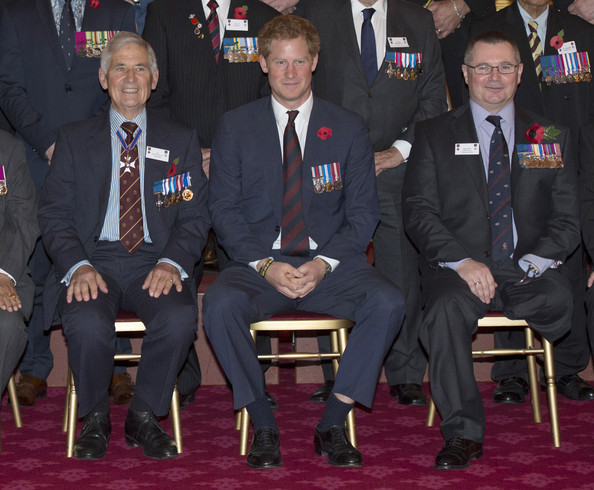 Prince Harry sits next to Jim Beaton GC (former Royal Protection officer) and Major Peter Norton GC (R) as he hosts the President's Party in remembrance and re-dedication for members of the Victoria Cross and George Cross Association in the State Apartments at St James's Palace on October 29, 2014 in London, England.