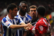 Marcus Williams of Sheffield United is confronted by Ben Marshall, Reda Johnson and Stephen Bywater of Sheffield Wednesday during the npower League One match between Sheffield United and Sheffield Wednesday at Bramall Lane on October 16, 2011 in Sheffield, England.