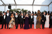 """(L-R) Producer Simon Emanuel, Joonas Suotamo, Thandie Newton, Woody Harrelson, Ron Howard, Emilia Clarke, Alden Ehrenreich, Donald Glover, Chewbacca and (in costume), Paul Bettany and Phoebe Waller-Bridgeattends the screening of """"Solo: A Star Wars Story"""" during the 71st annual Cannes Film Festival at Palais des Festivals on May 15, 2018 in Cannes, France."""