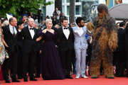 """(L-R) Woody Harrelson, Ron Howard, Emilia Clarke, Alden Ehrenreich, Donald Glover and Chewbacca (in costume) attend the screening of """"Solo: A Star Wars Story"""" during the 71st annual Cannes Film Festival at Palais des Festivals on May 15, 2018 in Cannes, France."""
