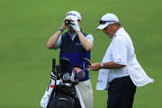 Justin Thomas of the United States uses a range finder as caddie Jimmy Johnson looks on during the pro-am prior to the Sony Open in Hawaii at the Waialae Country Club on January 08, 2020 in Honolulu, Hawaii.