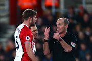 Cedric Soares and teammate Jack Stephens of Southampton confront referee Mike Dean during the Premier League match between Southampton and Brighton and Hove Albion at St Mary's Stadium on January 31, 2018 in Southampton, England.