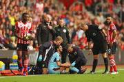 Referee Mike Dean speaks to George Boyd of Burnley as he is given treatment during the Premier League match between Southampton and Burnley at St Mary's Stadium on October 16, 2016 in Southampton, England.