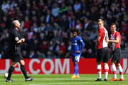Referee Mike Dean speaks to James Ward-Prowse of Southampton and Cedric Soares of Southampton during the Premier League match between Southampton and Chelsea at St Mary's Stadium on April 14, 2018 in Southampton, England.
