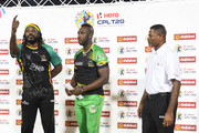In this handout image provided by CPL T20, Chris Gayle (L) of St Kitts & Nevis Patriots toss the coin as Andre Russell (C) of Jamaica Tallawahs and match referee Denavon Hayles (R) look on at the start of match 25 of the Hero Caribbean Premier League between St Kitts & Nevis Patriots and Jamaica Tallawahs at the Warner Park Sporting Complex on September 2, 2018 in Basseterre, St Kitts, Saint Kitts And Nevis.