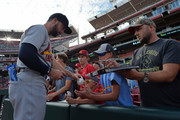 Greg Garcia #35 of the St. Louis Cardinals signs autographs for fans before a game against the Cincinnati Reds at Great American Ball Park on July 24, 2018 in Cincinnati, Ohio.