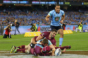 Josh Morris of the Blues scores a try against Greg Inglis of the Maroons (L) and Johnathan Thurston during game two of the State of Origin series between the New South Wales Blues and the Queensland Maroons at the Melbourne Cricket Ground on June 17, 2015 in Melbourne, Australia.