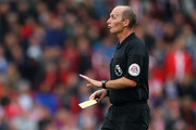 Referee Mike Dean shows a yellow card during the Premier League match between Stoke City and Chelsea at Bet365 Stadium on September 23, 2017 in Stoke on Trent, England.