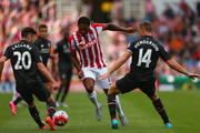 Glen Johnson of Stoke City goes between Jordan Henderson (14) and Adam Lallana of Liverpool (20) during the Barclays Premier League match between Stoke City and Liverpool at Brittania Stadium on August 9, 2015 in Stoke on Trent, England.