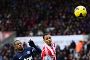 Peter Odemwingie of Stoke City challenges for the ball with Patrice Evra of Manchester United during the Barclays Premier League match between Stoke City and Manchester United at Britannia Stadium on February 1, 2014 in Stoke on Trent, England.