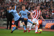 Charlie Adam of Stoke City and Ayoze Perez of Newcastle United battle for possession during the Premier League match between Stoke City and Newcastle United at Bet365 Stadium on January 1, 2018 in Stoke on Trent, England.