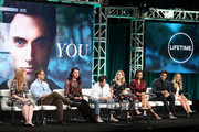 """(L-R) Sarah Schechter, Greg Berlanti, Sera Gamble, Penn Badgley, Elizabeth Lail, Shay Mitchell, John Stamos, and Caroline Kepnes of the television show """"You"""" speak during the A&E segment of the Summer 2018 Television Critics Association Press Tour at the Beverly Hilton Hotel on July 26, 2018 in Beverly Hills, California."""