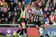 Sebastian Larsson of Sunderland and Hatem Ben Arfa of Newcastle challenge for the ball during the Barclays Premier League match between Sunderland and Newcastle United at Stadium of Light on October 27, 2013 in Sunderland, England.