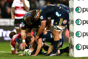 Ben Smith of the Highlanders is congratulated by Teihorangi Walden and Luke Whitelock after scoring a try during the round 12 Super Rugby match between the Highlanders and the Lions at Forsyth Barr Stadium on May 12, 2018 in Dunedin, New Zealand.