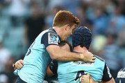 Andrew Kellaway, Matt Carraro and Dean Mumm of the Waratahs celebrate Matt Carraro scoring a try during the round six Super Rugby match between the New South Wales Waratahs and the Melbourne Rebels at Allianz Stadium on April 3, 2016 in Sydney, Australia.