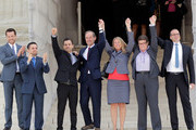 Members of the plaintiff team in the same sex marriage cases before the Supreme Court (L-R) Adam Umhoefer, executive director of the American Foundation for Equal Rights, plaintiff Paul Katami, plaintiff Jeff Zarillo, attorney David Boies, plaintiff Kris Perry, plaintiff Sandy Stier and Human Rights Campaign President Chad Griffin wave from the court's steps after favorable rulings were issued June 26, 2013 in Washington, DC. The high court ruled to strike down DOMA and determined the California's proposition 8 ban on same-sex marriage was not properly before them, declining to overturn the lower court's striking down of the law.