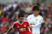 Ander Herrera of Manchester United is challenged by Sung-Yeung Ki of Swansea City during the Barclays Premier League match between Swansea City and Manchester United at Liberty Stadium on August 30, 2015 in Swansea, Wales.