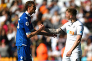 Peter Crouch of Stoke City shakes hands with Alfie Mawson of Swaansea City afterthe Premier League match between Swansea City and Stoke City at Liberty Stadium on May 13, 2018 in Swansea, Wales.