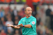 Referee Mike Dean makes a point during the Barclays Premier League match between Swansea City and Tottenham Hotspur at Liberty Stadium on October 4, 2015 in Swansea, Wales.