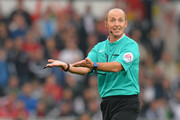 Referee Mike Dean reacts during the Barclays Premier League match between Swansea City and Tottenham Hotspur at Emirates Stadium on October 4, 2015 in Swansea, Wales.
