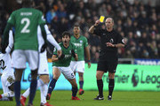 Claudio Yacob of West Bromwich Albion is shown the yellow card by referee Mike Dean during the Premier League match between Swansea City and West Bromwich Albion at Liberty Stadium on December 9, 2017 in Swansea, Wales.  (Photo by Stu Forster/Getty Images) *** Local Caption *** Claudio Yacob; Mike Dean