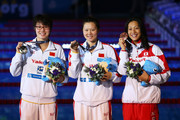 (L-R) Silver medal winner Yuanhui Fu of China, Gold medal winner Jing Zhao of China and Bronze medal winner Aya Terakawa of Japan celebrate on the podium after the Swimming Women's Backstroke 50m Final on day thirteen of the 15th FINA World Championships at Palau Sant Jordi on August 1, 2013 in Barcelona, Spain.
