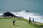 Patrick Reed of the United States putts on the seventh green as Phil Mickelson of the United States and Scott Ozanus, Deputy Chairman and Chief Operating Officer of KPMG, look on during the third round of the AT&T Pebble Beach Pro-Am at Pebble Beach Golf Links on February 09, 2019 in Pebble Beach, California.