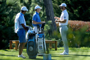 Jordan Spieth (L) and Dustin Johnson meet at the 17th tee during Round Two of the AT&T Pebble Beach Pro-Am at Monterey Peninsula Country Club on February 9, 2018 in Pebble Beach, California.