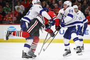 Braydon Coburn #55 (L) and Ryan Callahan #24 of the Tampa Bay Lightning collide with David Kampf #64 of the Chicago Blackhawks at the United Center on January 22, 2018 in Chicago, Illinois. The Lightning defeated the Blackhawks2-0.