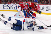 Cedric Paquette #54 of the Tampa Bay Lightning falls to the ice reaching for the puck against Andrei Markov #79 of the Montreal Canadiens in Game Three of the First Round of the 2014 NHL Stanley Cup Playoffs at the Bell Centre on April 20, 2014 in Montreal, Quebec, Canada.