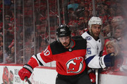 Marcus Johansson #90 of the New Jersey Devils hits Dan Girardi #5 of the Tampa Bay Lightning into the boards during the second period in Game Four of the Eastern Conference First Round during the 2018 NHL Stanley Cup Playoffs at the Prudential Center on April 18, 2018 in Newark, New Jersey.
