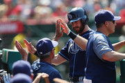 Evan Longoria #3 of the Tampa Bay Rays celebrates in the dugout after scoring a third run for his team in the ninth inning against the Los Angeles Angels at Angel Stadium of Anaheim on July 16, 2017 in Anaheim, California.
