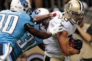 Jimmy Graham #80 of the New Orleans Saints carries the ball as Jason McCourty #30 of the Tennessee Titans and Bernard Pollard #31 of the Tennessee Titans defend during the first preseason game between the New Orleans Saints and the Tennessee Titans at Mercedes-Benz Superdome on August 15, 2014 in New Orleans, Louisiana.