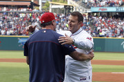 Former Indians great Jim Thome #25 is met by Indians player Jason Giambi #25 after Giambi relinquished his number 25 so that Thome, who announced his retirement today, could retire as an Indian with his playing number 25 before the game between the Cleveland Indians and the Texas Rangers on August 2, 2014 at Progressive Field in Cleveland, Ohio.