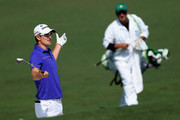 Justin Rose of England reacts to a shot as caddie Mark Fulcher looks on during a practice round prior to the start of the 2012 Masters Tournament at Augusta National Golf Club on April 4, 2012 in Augusta, Georgia.