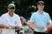 Justin Rose of England (R) waits on the fourth tee with caddie Mark Fulcher (L) during the first round of the 2012 Masters Tournament at Augusta National Golf Club on April 5, 2012 in Augusta, Georgia.