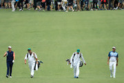 Justin Rose of England and Bubba Watson of the United States walk with their caddies Mark Fulcher and Ted Scott on the seventh hole during the third round of the 2018 Masters Tournament at Augusta National Golf Club on April 7, 2018 in Augusta, Georgia.
