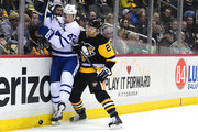 Tyler Bozak #42 of the Toronto Maple Leafs is checked into the boards by Chad Ruhwedel #2 of the Pittsburgh Penguins at PPG PAINTS Arena on December 9, 2017 in Pittsburgh, Pennsylvania.
