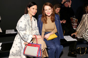 Lucy Liu (L) and Julianne Moore attend the Tory Burch Fall Winter 2020 Fashion Show at Sotheby's on February 09, 2020 in New York City.