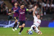 Harry Winks of Tottenham Hotspur tackles Lionel Messi of Barcelona during the Group B match of the UEFA Champions League between Tottenham Hotspur and FC Barcelona at Wembley Stadium on October 3, 2018 in London, United Kingdom.